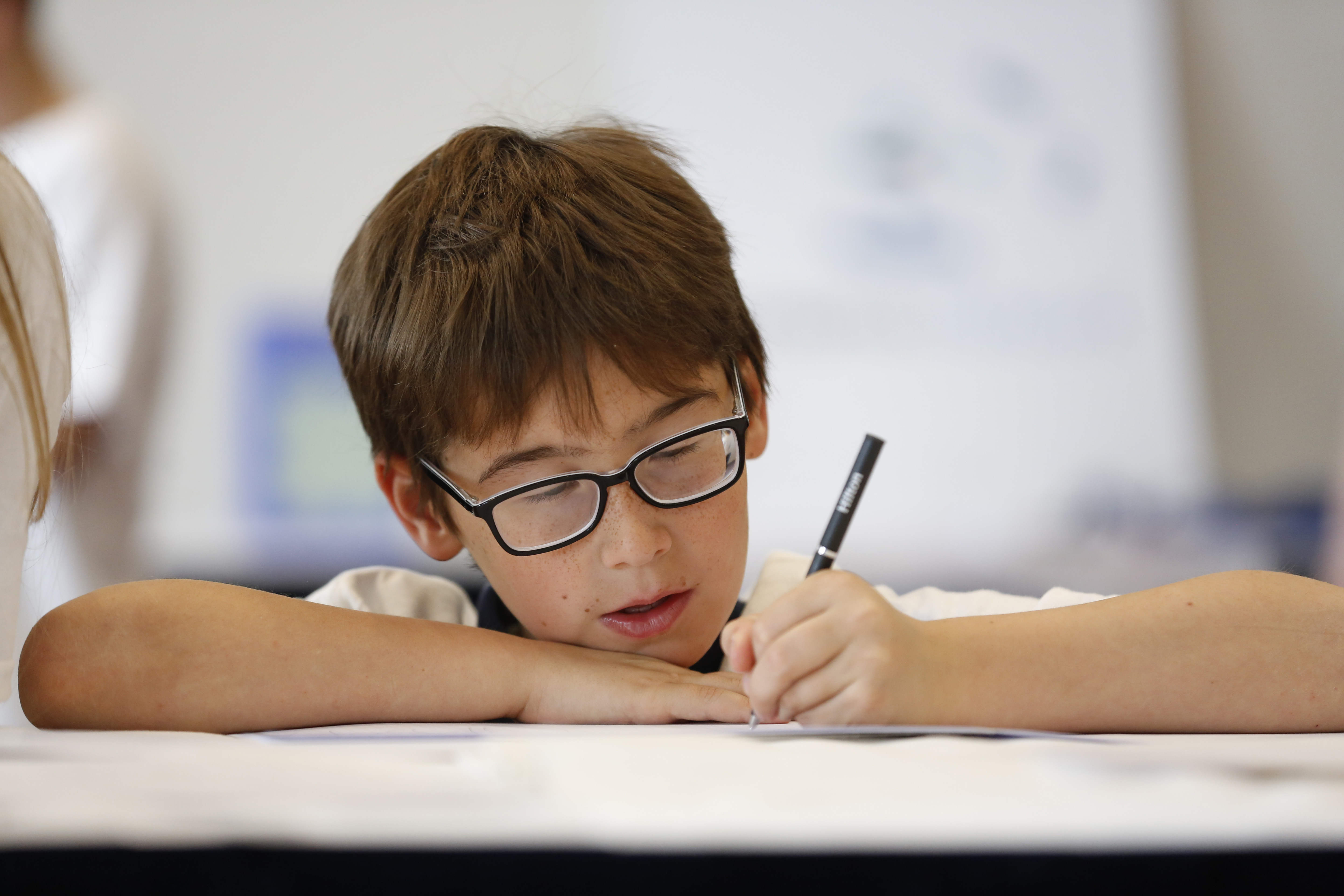 A boy wearing glasses, writing.