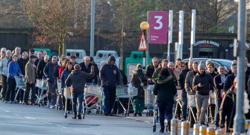People queue with trolleys in a supermarket car park