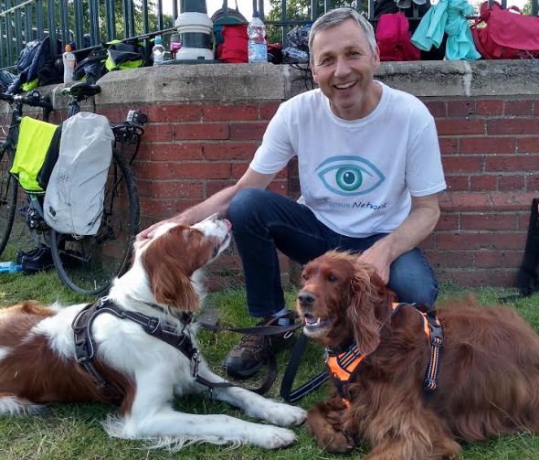 Tim in his Nystagmus Network T shirt with 2 dogs.