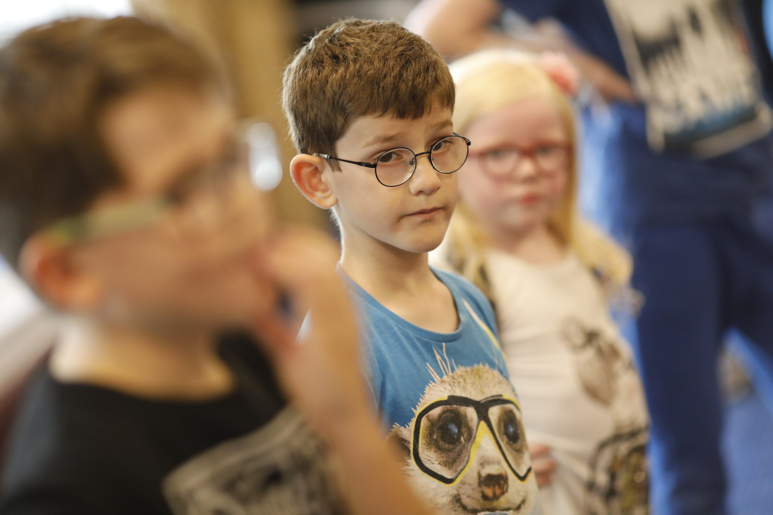 Children wearing glasses stand together.