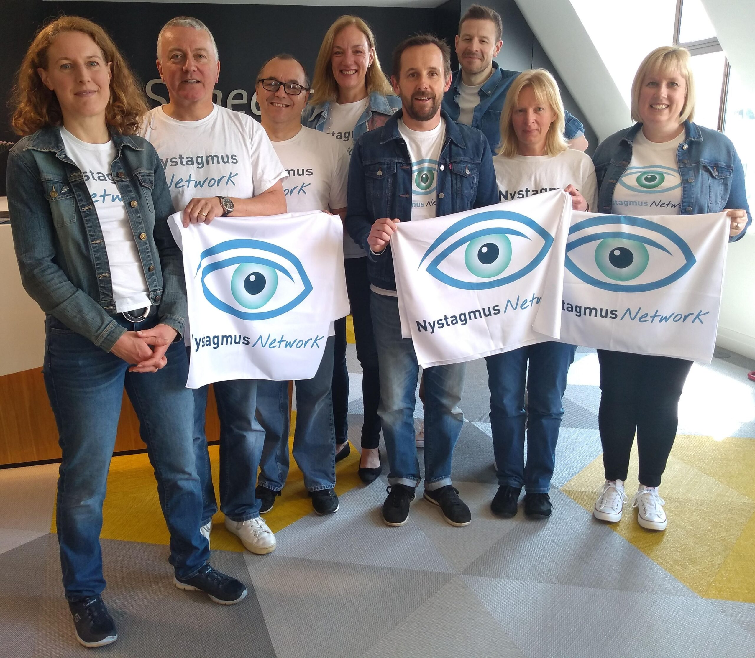 The Nystagmus Network trsutees and staff hold Nystagmus Network banners and smile at the camera.