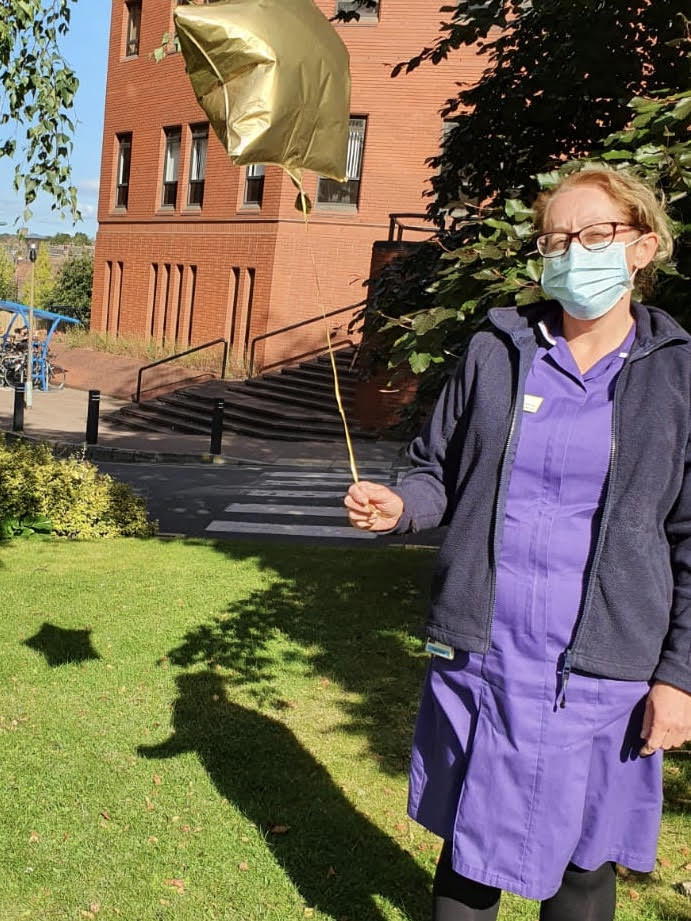 Tracey is wearing her nurse's uniform and a face mask and carrying a gold helium balloon.
