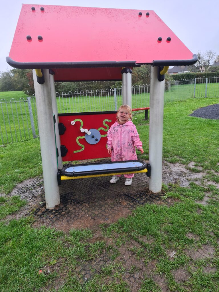 Mila-Eve is standing in a playhouse at the park. She is smiling at the camera.