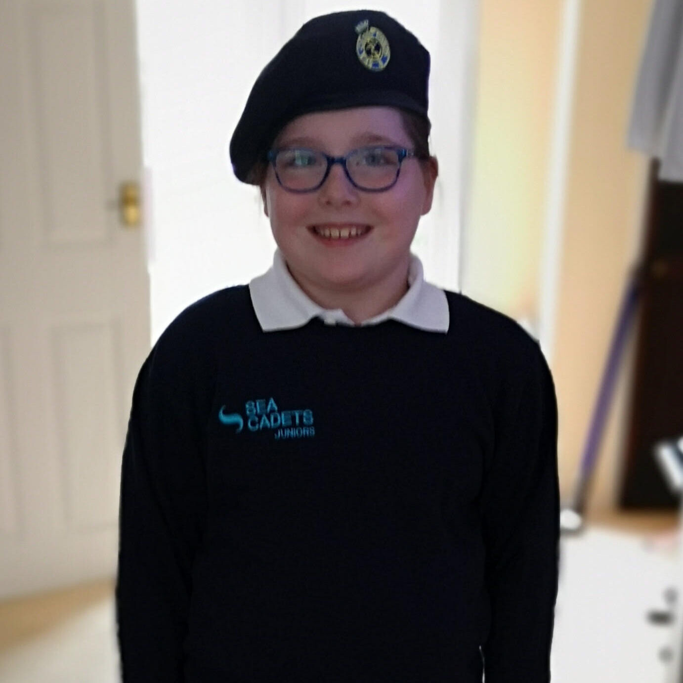 Eleanor is wearing her sea cadet uniform and smiling at the camera.