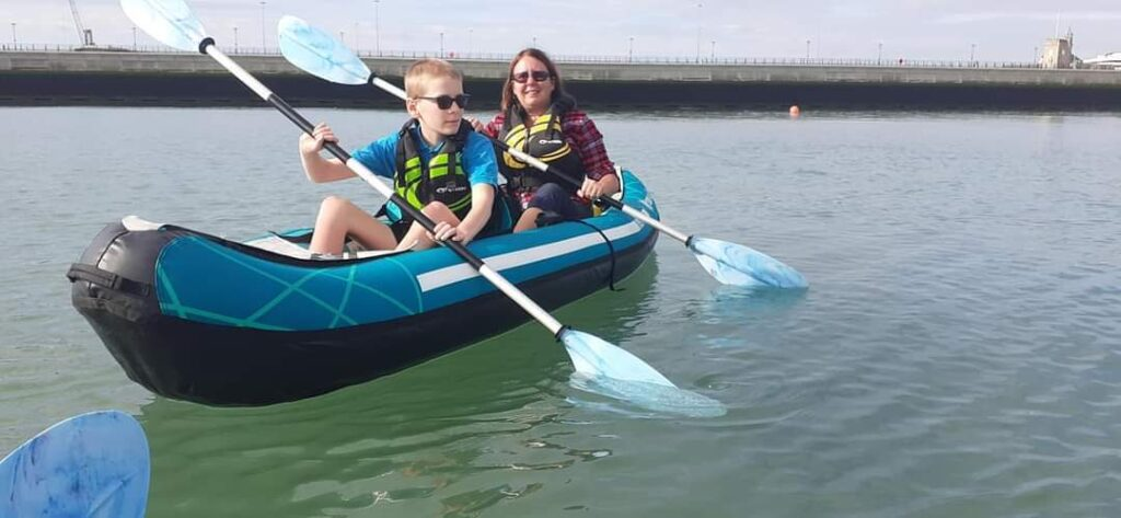 Hazel and Andrew are rowing a kayak on open water.