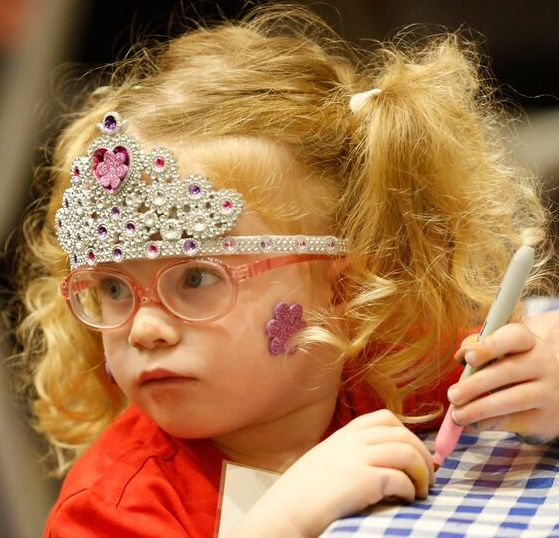 A small child is wearing a crown and pink glasses and drawing.