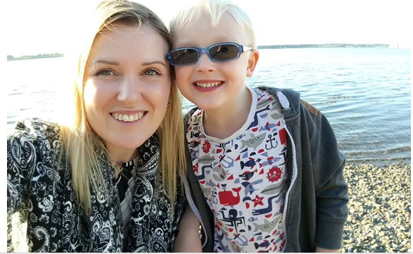 Claire and her young son smile for the camera