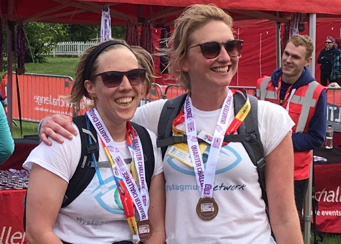 2 runners in Nystagmus Network T-shirts wearing their finishers' medals