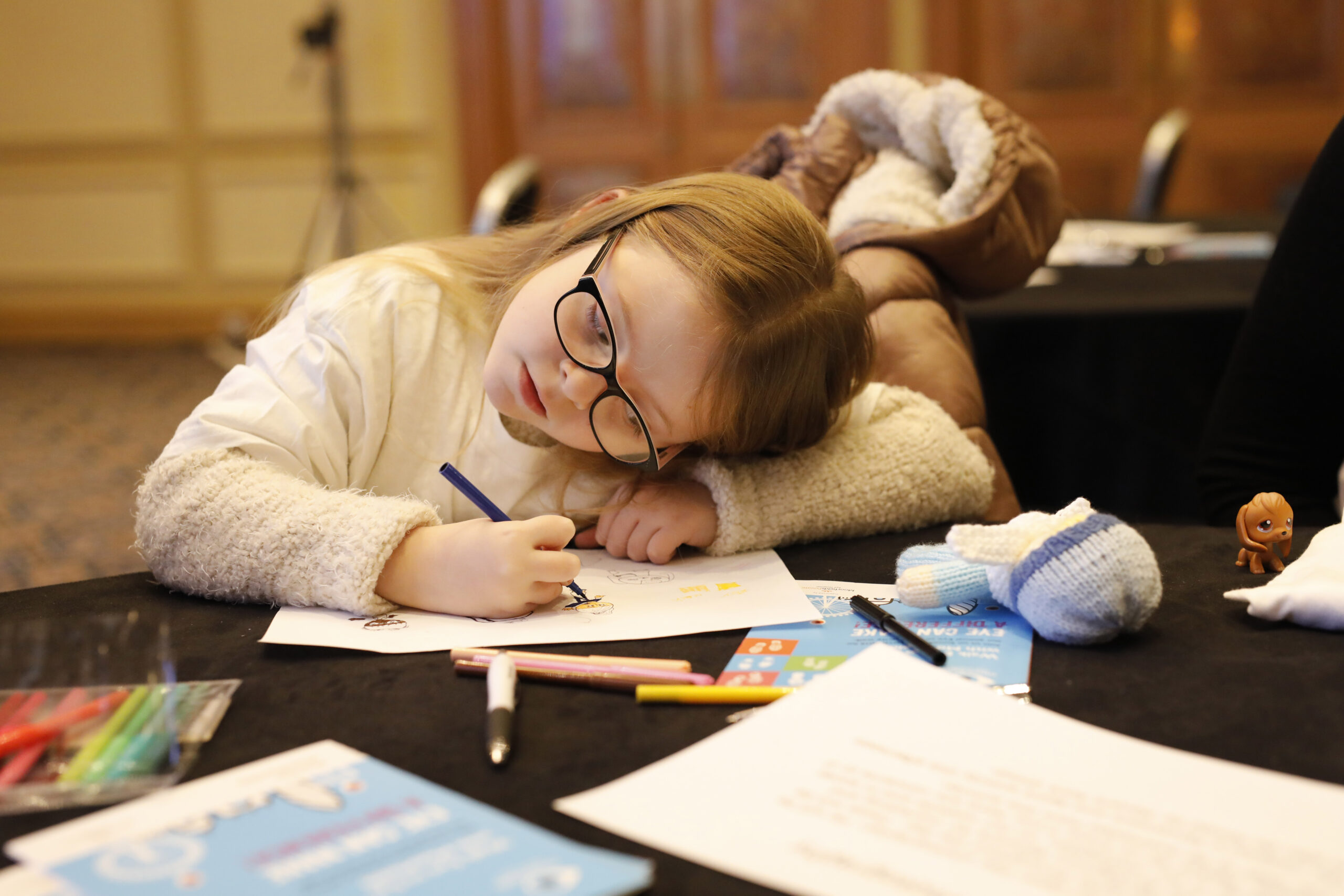 A child wearing glasses using her nullpoint as she writes.