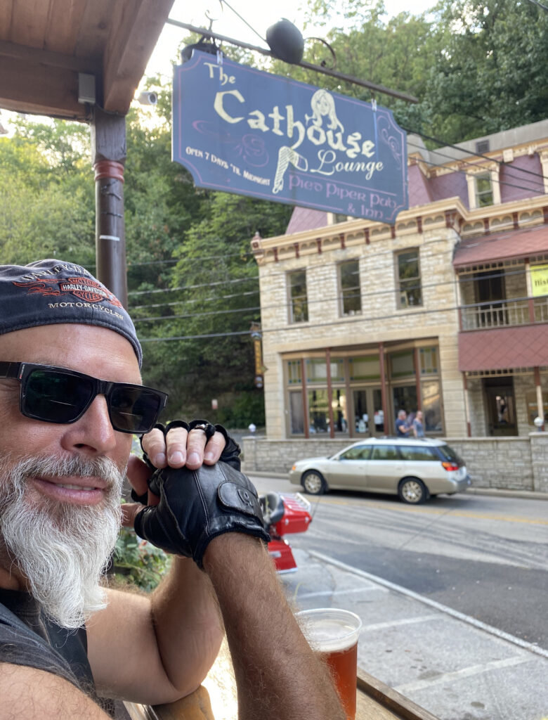Edwin smiles at the camera. He is wearing dark glasses, leather gloves and a bandana.
