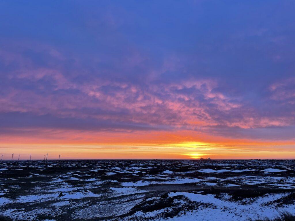 A sunset over a snowy landscape.