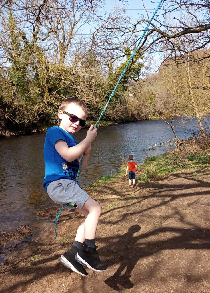 Grayson enjoys a rope swing by a lake. He is wearing dark glasses.