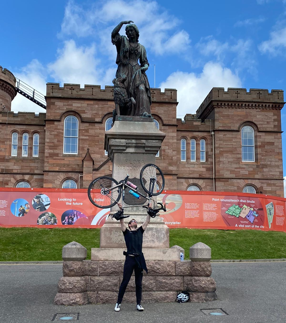 Sam Jones holds his bicycle above his head to celebrate completing his NC 500.