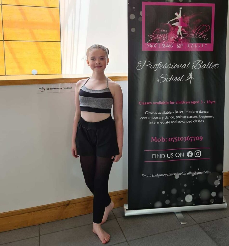 Poppy in dance training outfit stands in a balletic pose beside a banner.