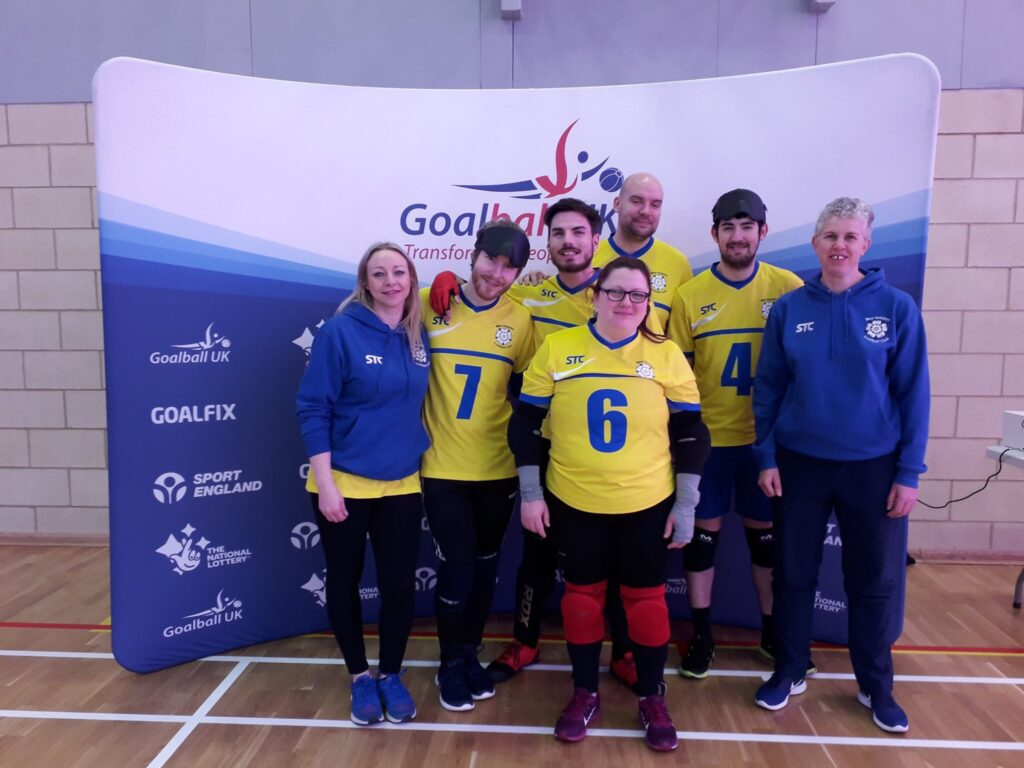 Kathryn and her team pose in front of a Goalball UK banner.